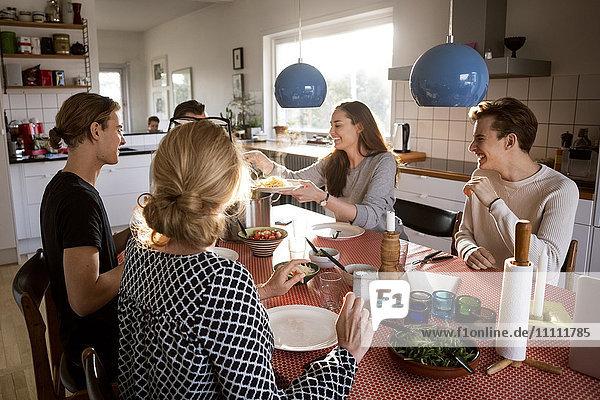 Frau serviert Essen für die Familie am Esstisch
