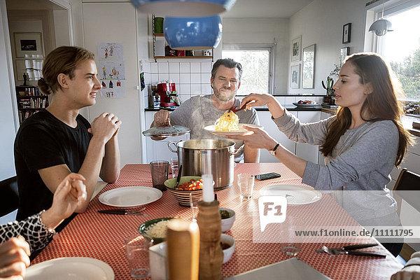 Frau serviert Essen im Teller  während sie mit der Familie am Esstisch sitzt.