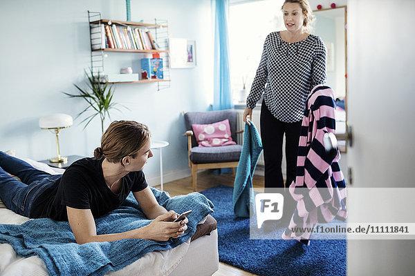 Wütende Frau  die Kleidung hält  während sie den Sohn sieht  der im neuen Zuhause auf dem Bett liegt.