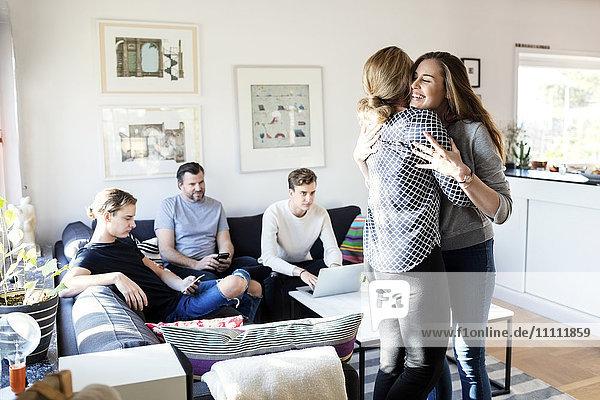 Mutter und Tochter umarmen sich  während die Familie auf dem Sofa im Wohnzimmer sitzt.
