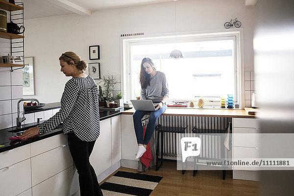 Mutter arbeitet  während Tochter mit Laptop in der Küche in der neuen Heimat