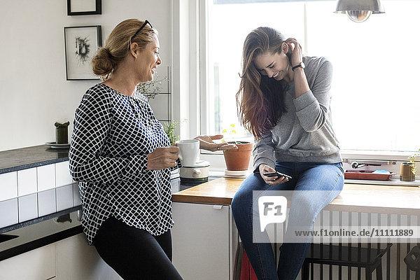 Mutter im Gespräch mit glücklicher Tochter über Smartphone in der Küche