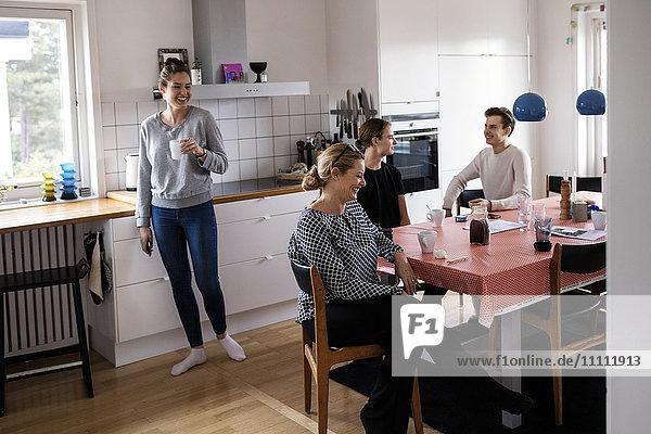 Glückliche Familie  die ihre Freizeit in der Küche des neuen Heims verbringt.
