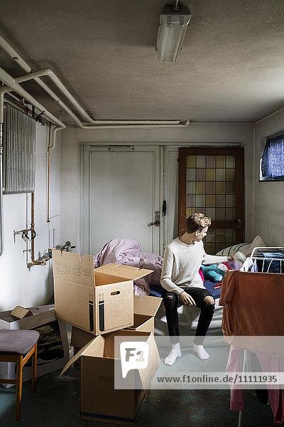 Volle Länge des Mannes  der auf dem Bett sitzt  während er das neue Haus verlegt.