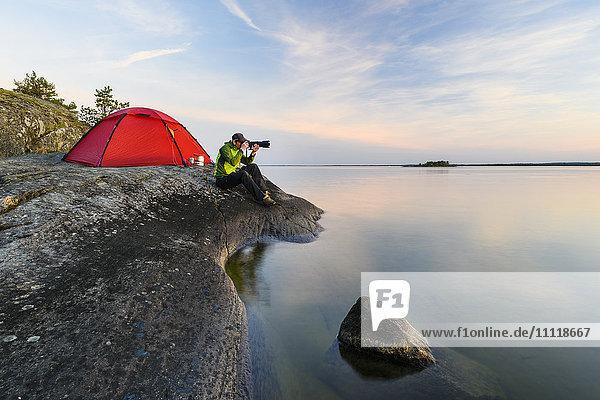 Man near tent at rocky coast