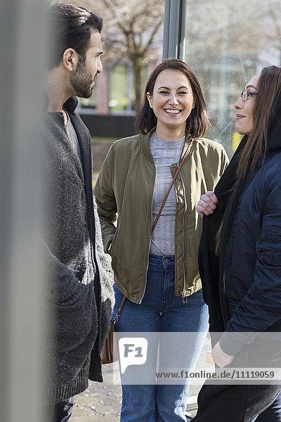 Friends talking on bus stop