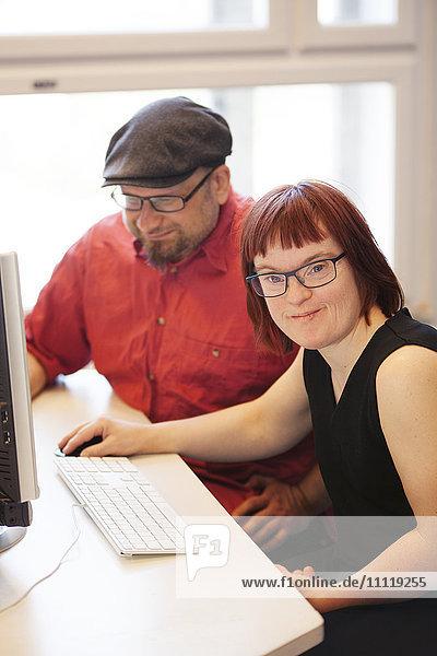 Schweden  Frau mit Down-Syndrom bei der Arbeit am Computer mit Kollegen