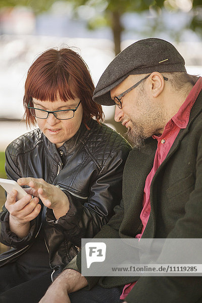 Sweden  Sodermanland  Woman with down syndrome sitting and checking smart phone together with boyfriend
