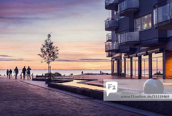 Schweden  Öresundregion  Skane  Malmö  Vastra hamnen  Silhouetten von Menschen bei Sonnenuntergang