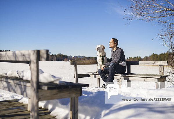 Sweden,  Vasterbotten,  Umea,  Man sitting on bench with dog in winter