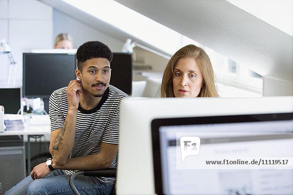 Schweden  Zwei Büroangestellte beim Blick auf den Bildschirm im Büro