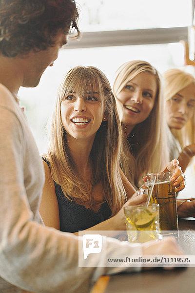 Schweden  Mann im Gespräch mit Frauen in der Bar