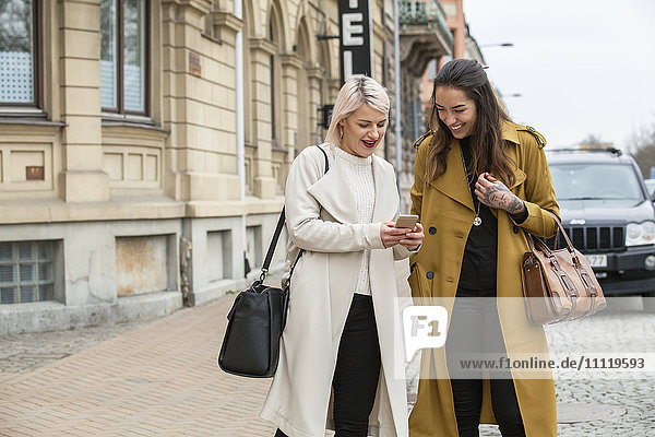 Sweden  Skane  Kirstianstad  Two women looking at smart phone on street