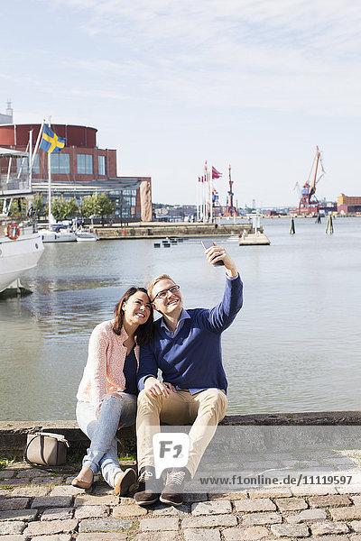 Schweden  Vastergotland  Göteborg  Junges Paar sitzt auf der Promenade und nimmt Selfie mit Smartphone.