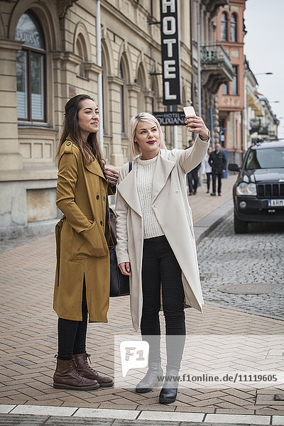 Schweden  Skane  Kirstianstad  Zwei junge Frauen beim Selbstfotografieren auf der Straße
