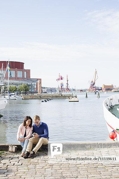 Schweden  Vastergotland  Göteborg  Junges Paar sitzt auf der Promenade am Hafen und überprüft Smartphone