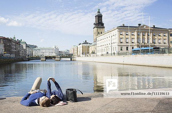 Schweden  Vastergotland  Göteborg  Junges Paar auf der Promenade liegend und mit Selbstbedienung