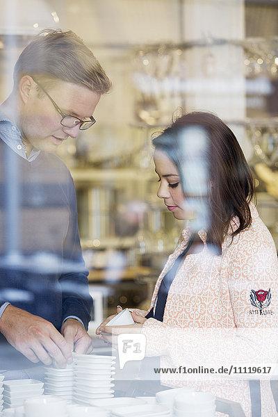 Schweden  Junges Paar wählt Porzellanschalen im Geschäft