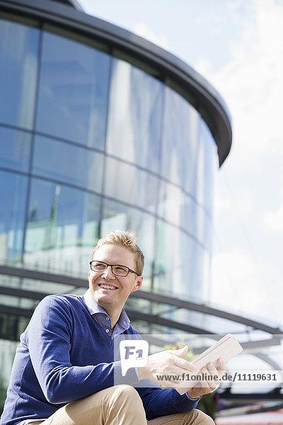 Schweden  Vastergotland  Göteborg  Lächelnder junger Mann sitzt gegen Glasgebäude und benutzt digitale Tablette