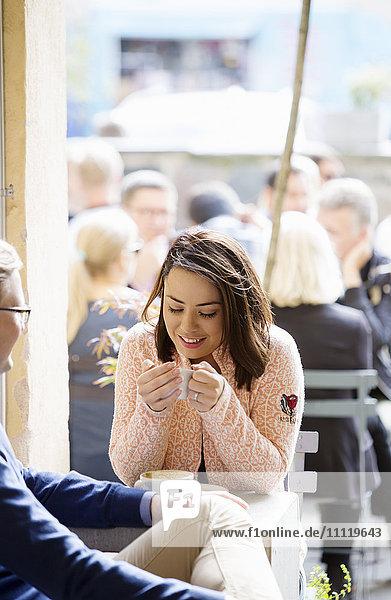 Schweden  Vastergotland  Junges Paar trinkt Kaffee im Café und unterhält sich