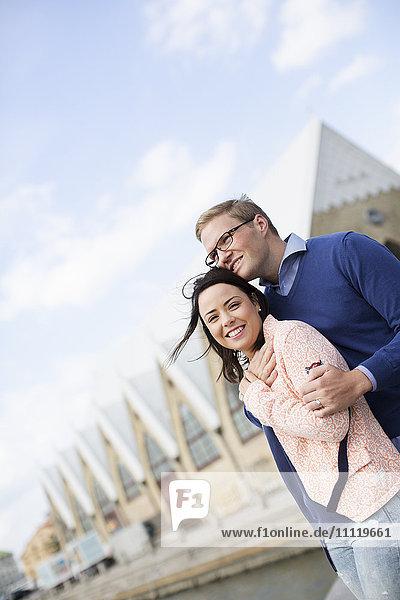Schweden  Vastergotland  Lächelndes junges Paar gegen Gebäude