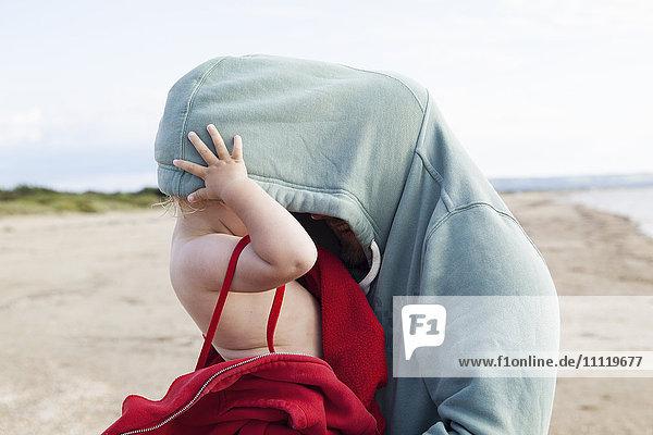 Schweden  Halland  Mellbystrand  Girl (2-3) versteckt in father´s Kapuzenshirt