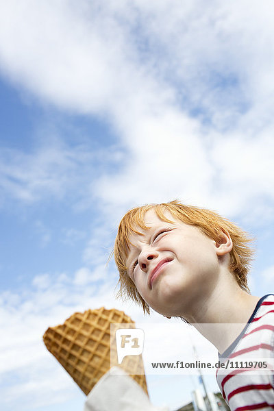Schweden  Tiefblick auf den rothaarigen Jungen (6-7)  der Eis gegen den Himmel isst.