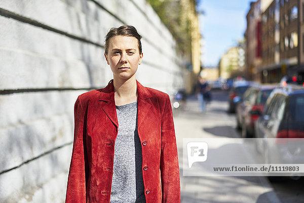 Sweden  Uppland  Stockholm  Kungsholmen  Woman in red jacket looking at camera