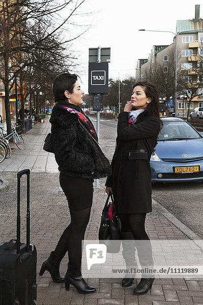 Schweden  Stockholm  Frauen im Gespräch auf dem Bürgersteig