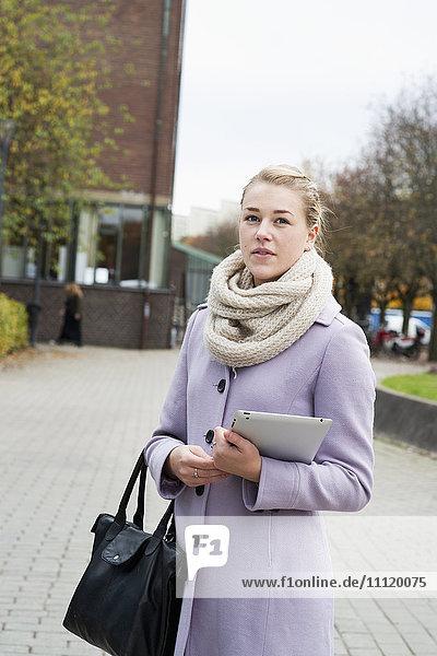 Schweden  Vastra Gotaland  Göteborg  Junge Frau im Mantel auf dem Bürgersteig stehend mit digitalem Tablett in der Hand