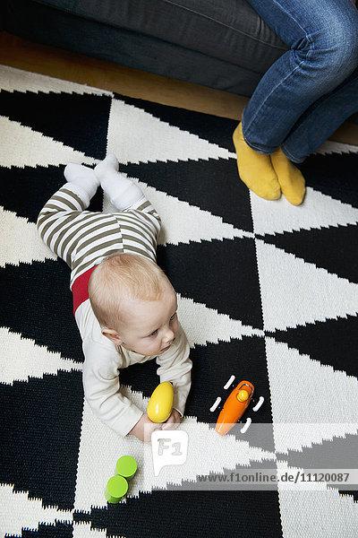 Schweden  Kleiner Junge (6-11 Monate) auf dem Teppich liegend und mit Spielzeug spielend
