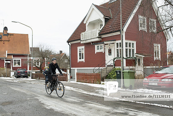 Schweden  Sodermanland  Stockholm  Fahrradfrau mit Tochter (2-3) auf Rücksitz