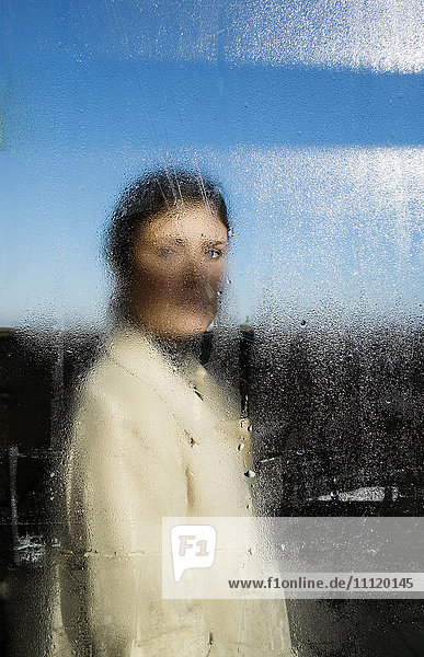 Schweden  Junge Frau im Mantel hinter nassem Fenster Schweden, Junge Frau im Mantel hinter nassem Fenster