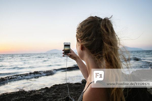 Griechenland  Kalymnos  Junge Frau fotografiert Sonnenuntergangshimmel mit Smartphone