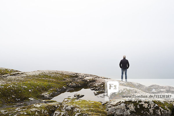 Schweden  Mann steht auf Felsrand und schaut in den Himmel