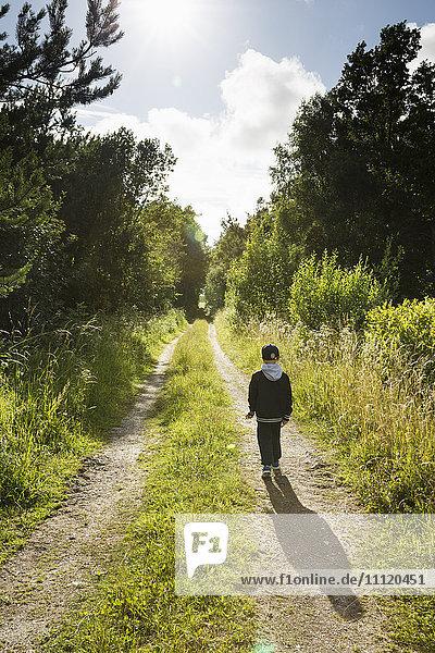 Sweden  Gotland  Boy (6-7) walking on dirt road among trees