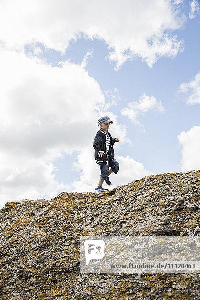 Sweden  Gotland  Boy (6-7) walking on top of cliff