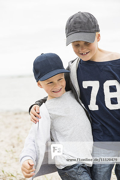 Sweden  Gotland  Smiling boys (6-7  8-9) in baseball caps at seashore
