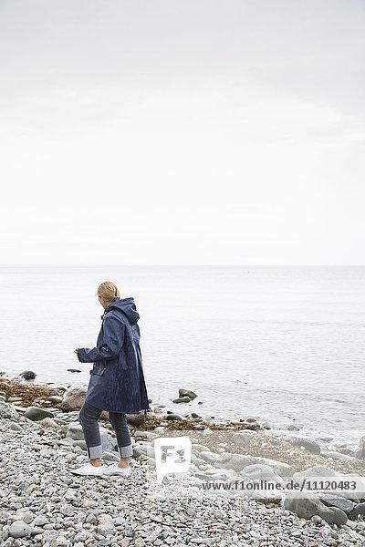 Sweden  Gotland  Mature woman in raincoat walking on rocky beach