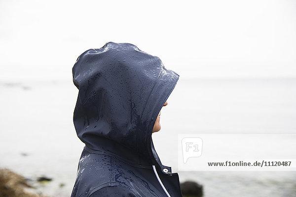 Schweden  Gotland  Reife Frau in Kapuze am Strand