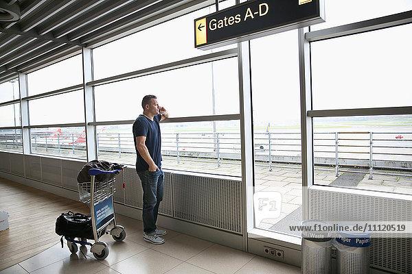 Deutschland  Hamburg  reifer Mann beim Telefonieren am Flughafen