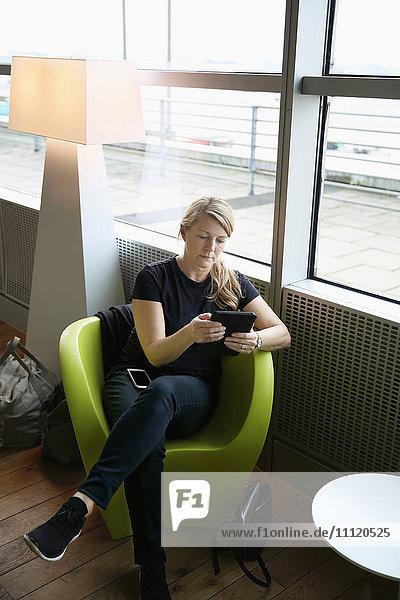 Germany  Hamburg  Mature woman sitting at airport hall and using tablet
