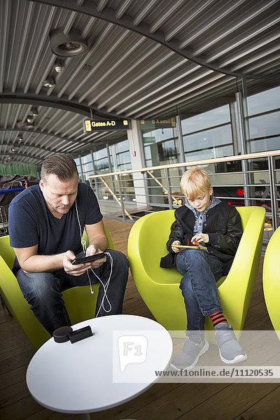 Germany  Hamburg  Mature man and boy (8-9) sitting at airport hall and using tablets