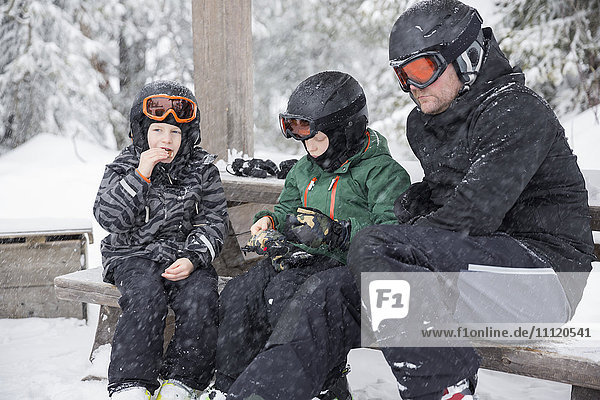 Sweden  Dalarna  Salen  Mature man and boys (6-7  8-9) wearing helmets and goggles sitting on bench surrounded by winter landscape