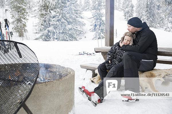 Sweden  Dalarna  Salen  Mature man hugging boy (6-7) sitting on bench by bonfire surrounded by winter landscape