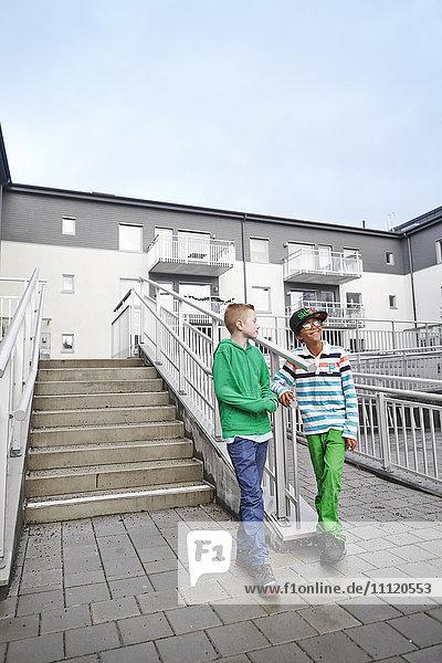 Schweden  Vastra Gotaland  Grimmered  Jungen (8-9) beim Treppensteigen und Sprechen