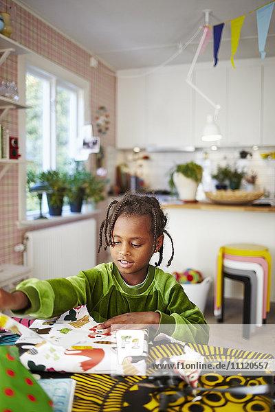 Schweden  Mädchen (6-7) beim Spielen mit Dekorpapier in der Küche