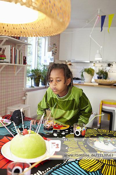 Schweden  Mädchen (6-7) beim Kerzenblasen auf Geburtstagskuchen