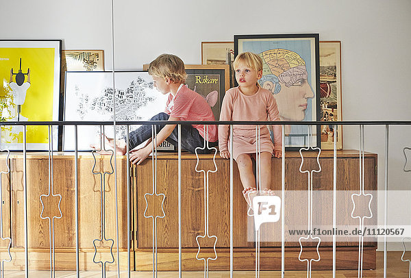 Schweden  Mädchen und Junge sitzend auf Schrank mit Bildern hinter dem Geländer
