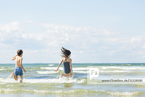 Schweden  Oland  Kopingsvik  Mädchen (10-11) und Junge (8-9)  die ins Meer rennen.